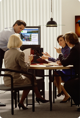 Employees having a meeting in front of a computer screen