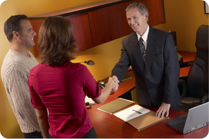 Man and woman shaking hands with business man